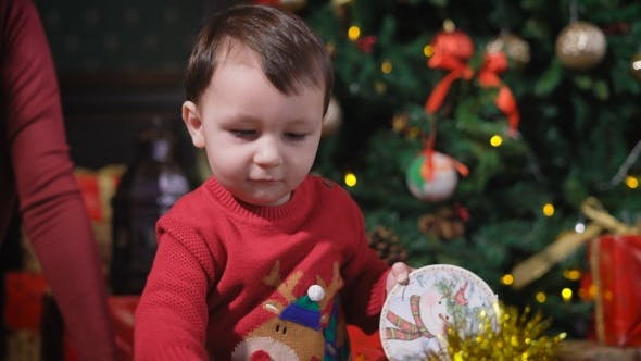 Thumbnail for Little Boy with Dark Hair, Wearing a Red Sweater, Deer Playing with Yellow Shiny Christmas Garland
