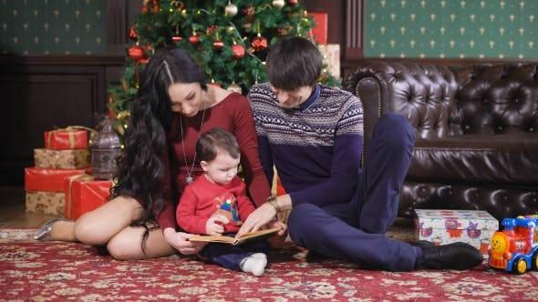 Thumbnail for Christmas Room. The Family Has Gathered Around a New Year Tree. The Kid Holds the Book in Hand