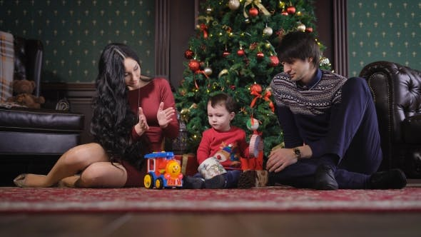 Thumbnail for Happy Family in Christmas Studio. The Studio Is Beautifully Decorated. Against the Wall Is Very
