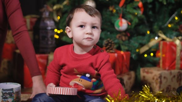 Cover Image for The Kid at the Christmas Tree. Interested Baby Playing with a Gift Box