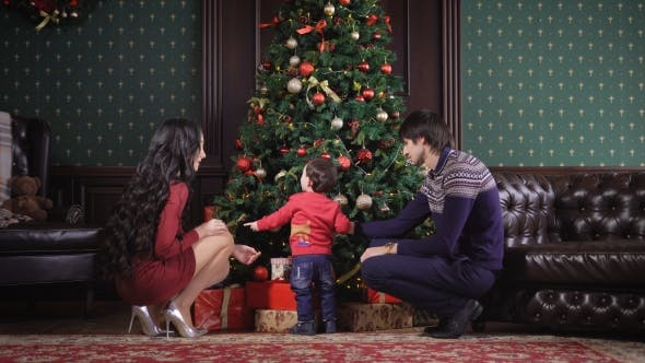 Thumbnail for Young Family Sits Near the Rich Christmas Tree. It Is Decorated Garland, Toys, Ribbons, Bows. Mom