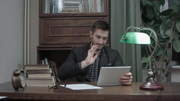 Thumbnail for Young Man Sitting at His Study Table and Having a Video Call Via Tablet