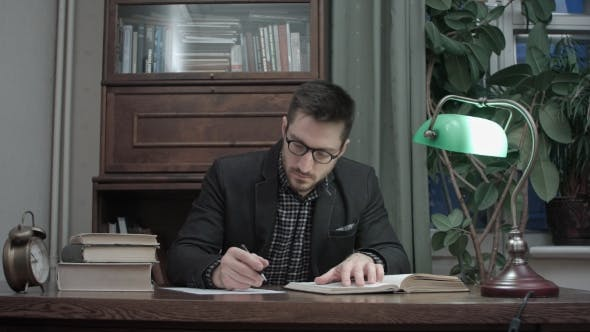 Thumbnail for Concentrated Male Researcher Reading Book and Making Notes at the Desk