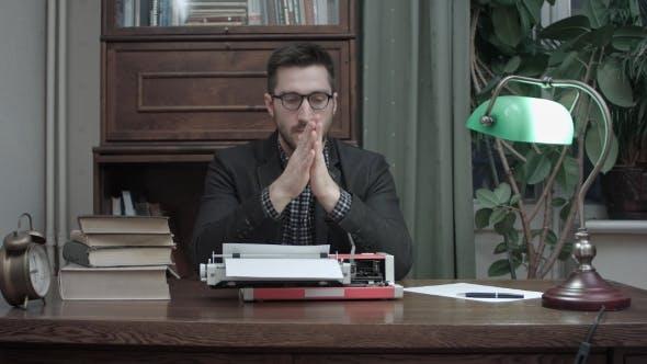Thumbnail for Nachdenklicher Schriftsteller sitzt vor Schreibmaschine wartet auf Inspiration für sein neues Buch