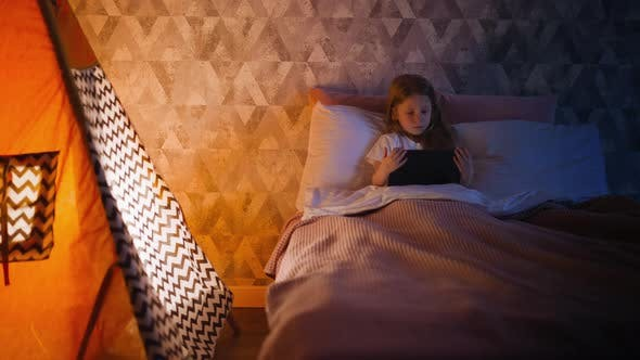 Little Child Watches Cartoons Lying in Bed By Play Tent