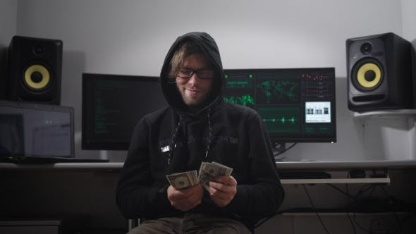 Thumbnail for A Man in a Jacket with a Hood in the Computer Room. Hacker in Glasses and with Money in Hand Sits on