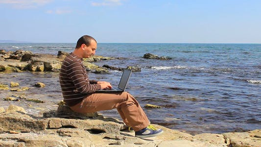 Thumbnail for Man Working With Laptop On A Rocky Beach