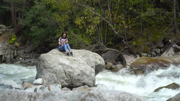 Thumbnail for A Young Girl Sits on a Stone with a Phone in Her Hands in the Mountains By the River. Travel To the