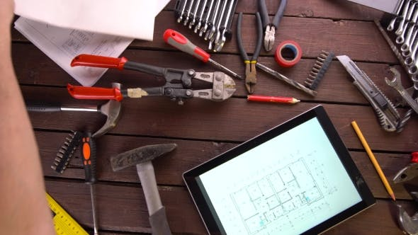 Cover Image for Mechanic Engineer Works with Tablet on His Desk