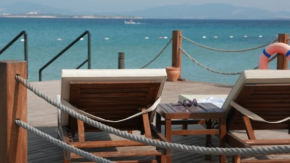 Thumbnail for View of the Emty Wooden Sunbeds and Coffee Table with a Sunglasses with Sea and Moving Boat on the