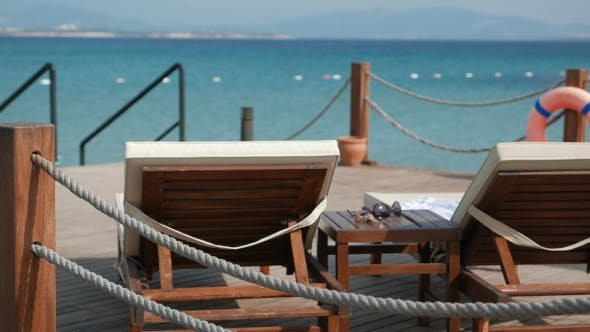 Thumbnail for Scene of a Sunny Day with Empty Wooden Deck Chairs and Coffee Table with a Sunglasses and Shells