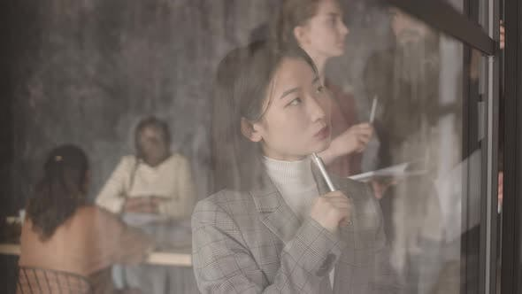 Pensive Asian Businesswoman Behind Glass Wall