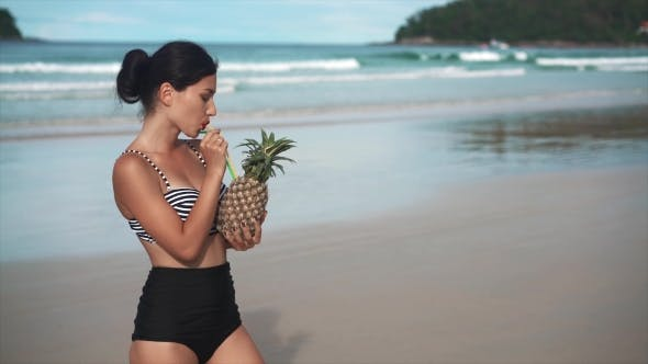Thumbnail for Happy Girl Holding a Pinapple Cocktail on a Beach