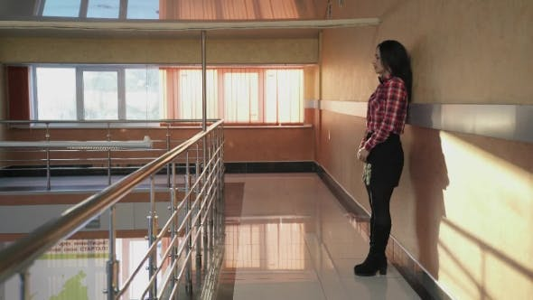 Thumbnail for Young Woman Desperate To Sit Down on a Wall in an Empty Corridor.