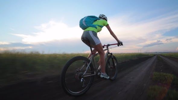 Thumbnail for Woman Cyclist Rides Bike a Dirt Road