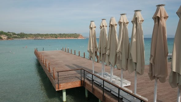 Thumbnail for Wooden Bathing Pier with Line of Umbrellas Ready for Swimming Season with Shore and Sea in a Sunny