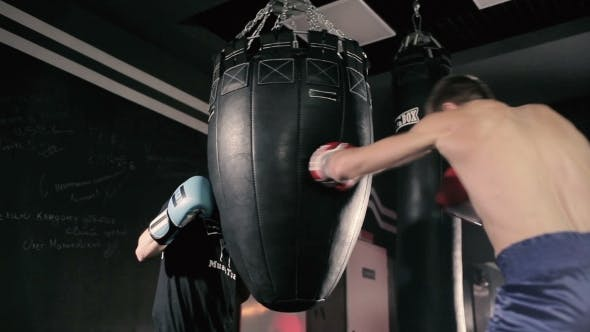 Thumbnail for Athlete Holds the Punching Bag for His Partner.