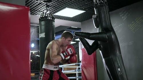 Athlete Strikes Hard on the Boxing Dummy.