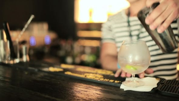 Thumbnail for Bartender Pours a Drink Into a Glass
