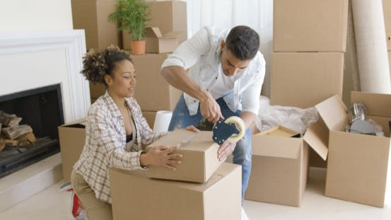Thumbnail for Young Couple Packing Boxes To Move Home