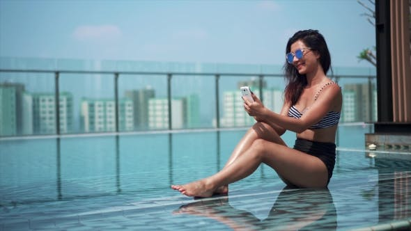 Thumbnail for Happy Woman Using a Mobile Phone in a Poolside