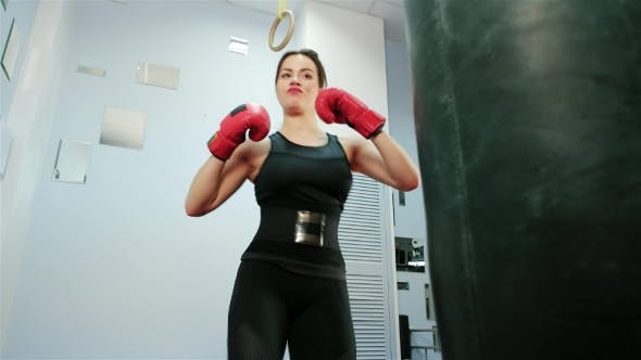 Cover Image for Female Boxer, Self-defense Training in the Gym, Girl in Boxing Gloves for Sports, Kicking on the