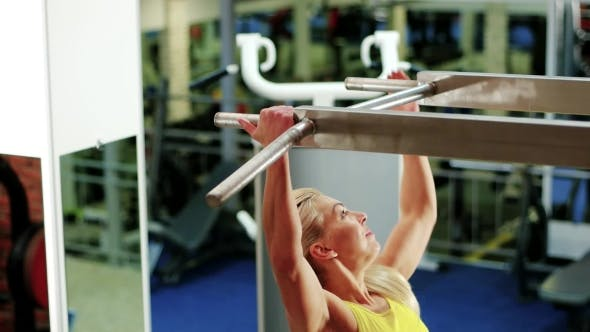 Thumbnail for Athletic Woman at the Gym, Girl Performs a Pulling Up Exercise, Exercises on the Horizontal Bar