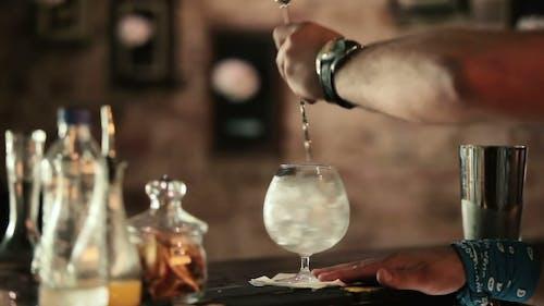 Barman wird in einem Glas Eiswürfel gemischt.