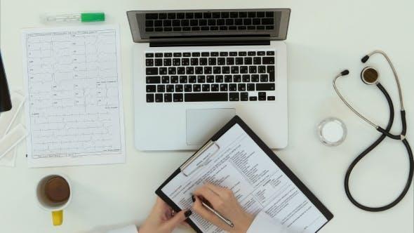 Thumbnail for Female Doctor Hands Filling up Medical History Form