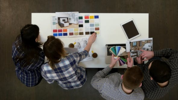 Designers Working in the Office with Layouts and Color Palette Answering Phone Calls and Clearing