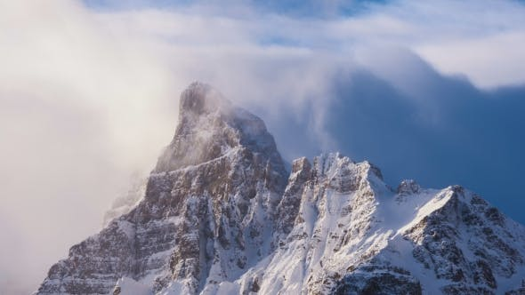 Thumbnail for Clouds Flowing Over Snowy Mountain Peak at Sunrise