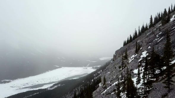 Thumbnail for Aerial Flyby of Edge of Snowy Rocky Mountain During Snow Storm