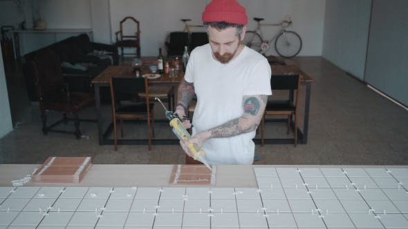 Thumbnail for Tattooed Man Applies Ceramic Tiles on Kitchen Table Set