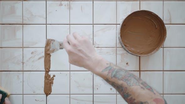 Thumbnail for Tattooed Man Applies Ceramic Tiles on Kitchen Table Set