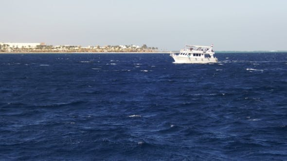 Thumbnail for Pleasure Boat Floats on the Waves of the Red Sea on the Background of Coast and Beaches in Egypt