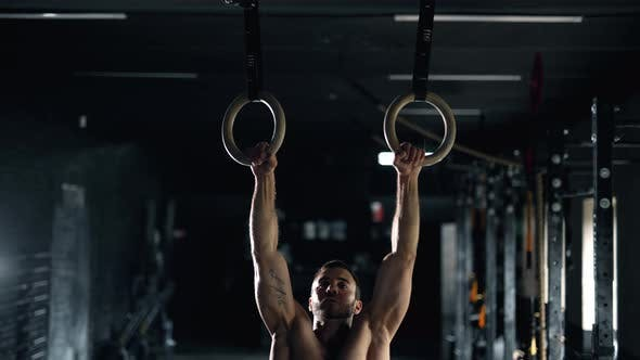 A Self Confident Muscular Sportsman is Doing Exercises Using Rings in the Gym
