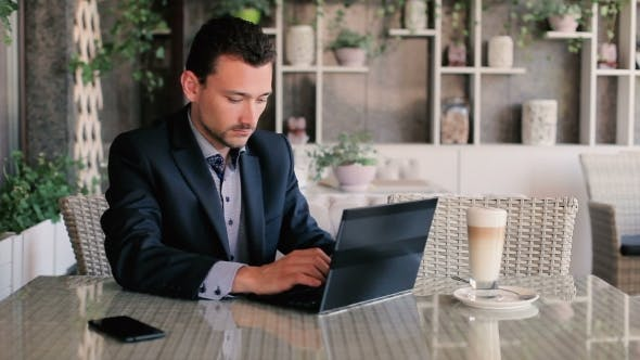 Cover Image for Young Businessman Working on Laptop in Restaurant