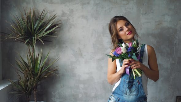 Thumbnail for Girl with Blond Hair and a Bunch of Flowers Tulips, Roses, on a Gray Background