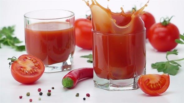 Cover Image for Ripe Tomato Falls into a Glass of Tomato Juice
