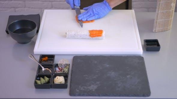 Cover Image for Koch Schneiden Sie das Filet von rotem Fisch mit Messer für die Sushi-Rolle