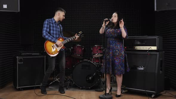 Pretty female solo singer with professional musician are enjoying live session