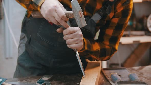 Carpentry Indoors - a Man Woodworker Making Notches with a Chisel and a Hammer on the Wooden Block