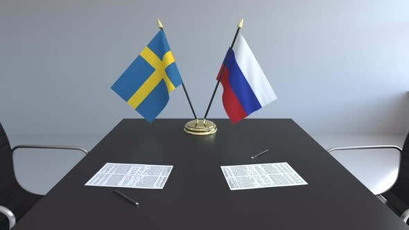 Flags of Sweden and Russia and Papers on the Table