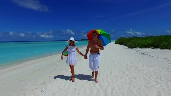 Young boy and girl on honeymoon vacation have fun on beach on summer white sandy 4K background