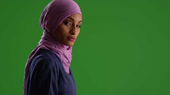Thumbnail for Female in purple headscarf looking at camera on green screen