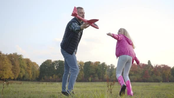 Thumbnail for Young Caucasian Father Playing with His Teen Blonde Daughter on the Autumn Meadow