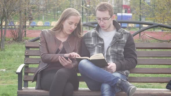 Thumbnail for Beautiful Couple Sitting on Bench in Park and Reading a Book
