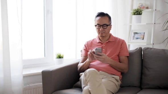 Thumbnail for Man with Smartphone Sitting on Sofa at Home 5