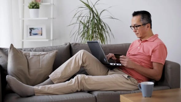 Cover Image for Man with Laptop and Credit Card on Sofa at Home 13
