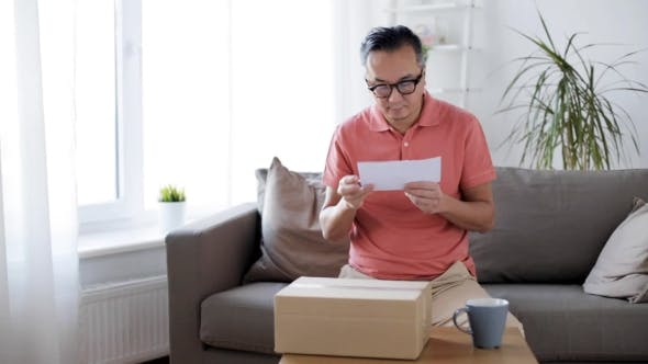 Thumbnail for Man Reading Invoice and Opening Box at Home 15